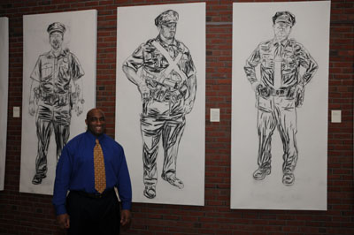 Northeastern Police Officer Mike Blue standing in front of his portrait.