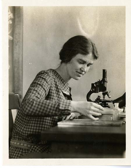 Black and white photograph of woman with microscope