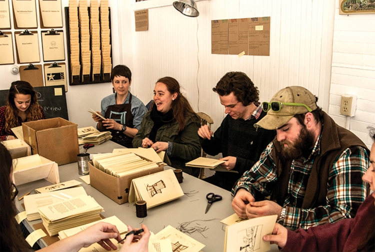 Chair City Oral History Book Series by Tracie Pouliot. Group bookbinding. The space I create as a community artist mimics factory culture and facilitates the spontaneous community building that happens when people work side-by-side making a meaningful product together. This group works together to collate, punch holes and bind the books.